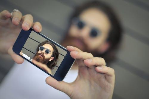 Man Wearing Black Sunglasses Taking a Selfie
