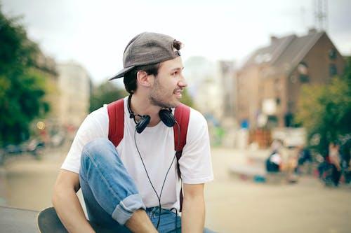 Man in White Shirt Wearing Black Cap and Black Headphones