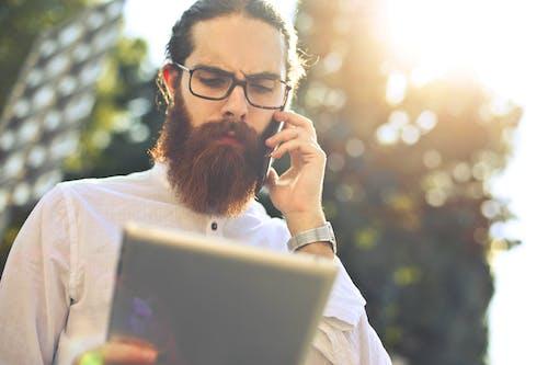Man Wearing Black Framed Eyeglasses Holding Silver Tablet Computer