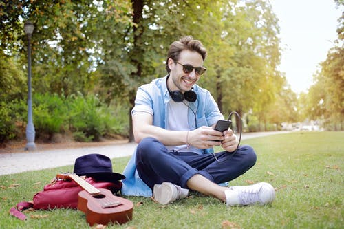 Man Using Smartphone Sitting Grass Field