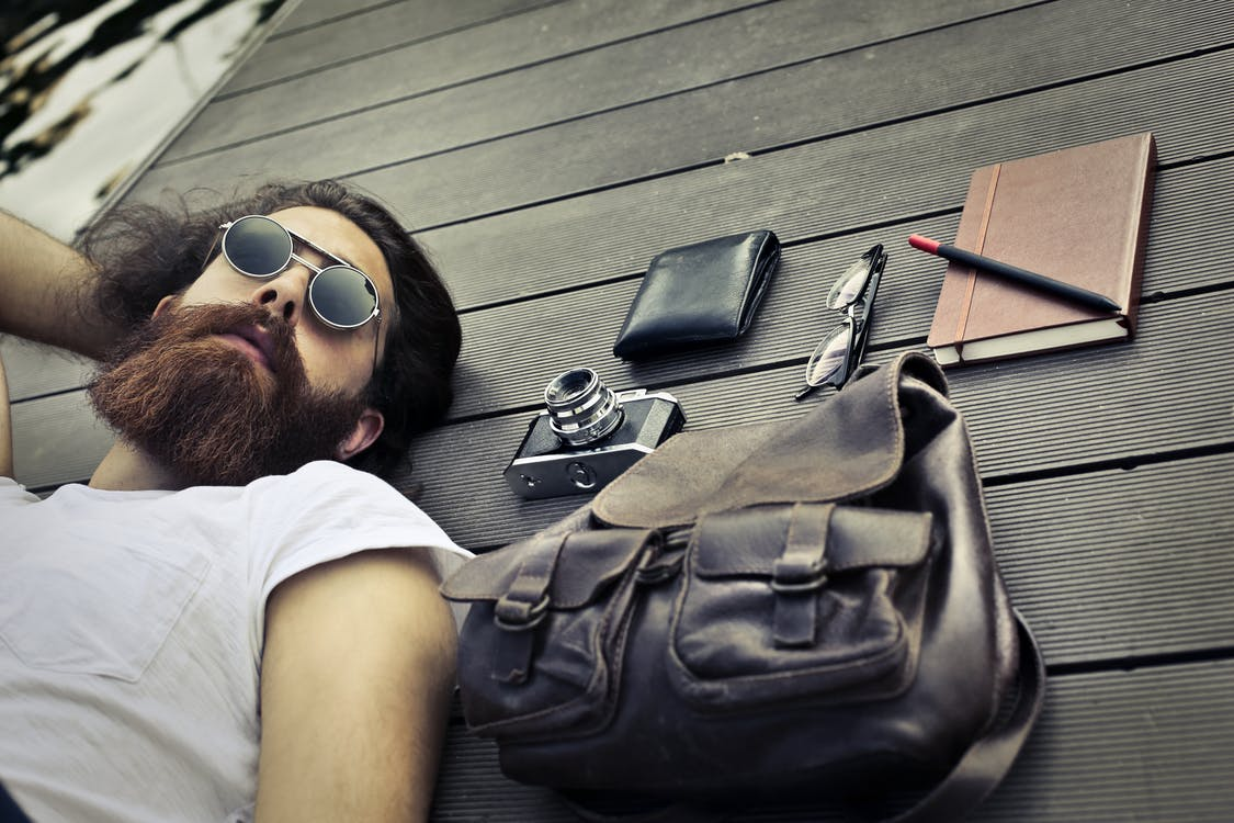 Man in White Crew Neck T-shirt Wearing Sunglasses Lying on Black wooden surface