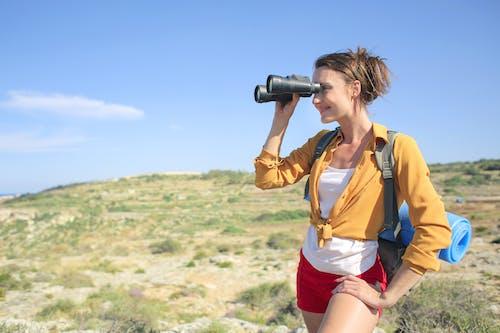 Woman in Yellow Long Sleeve is Holding Binocular