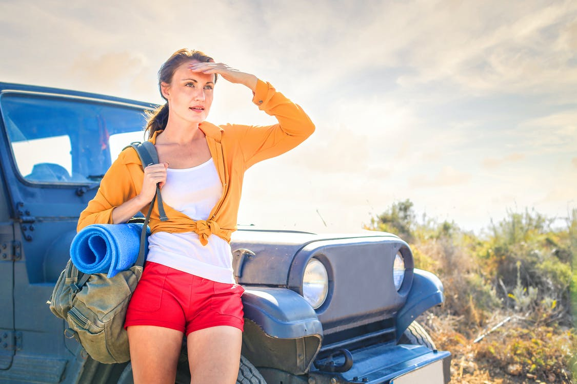 Woman in Yellow Long Sleeve Leaning on Blue Car
