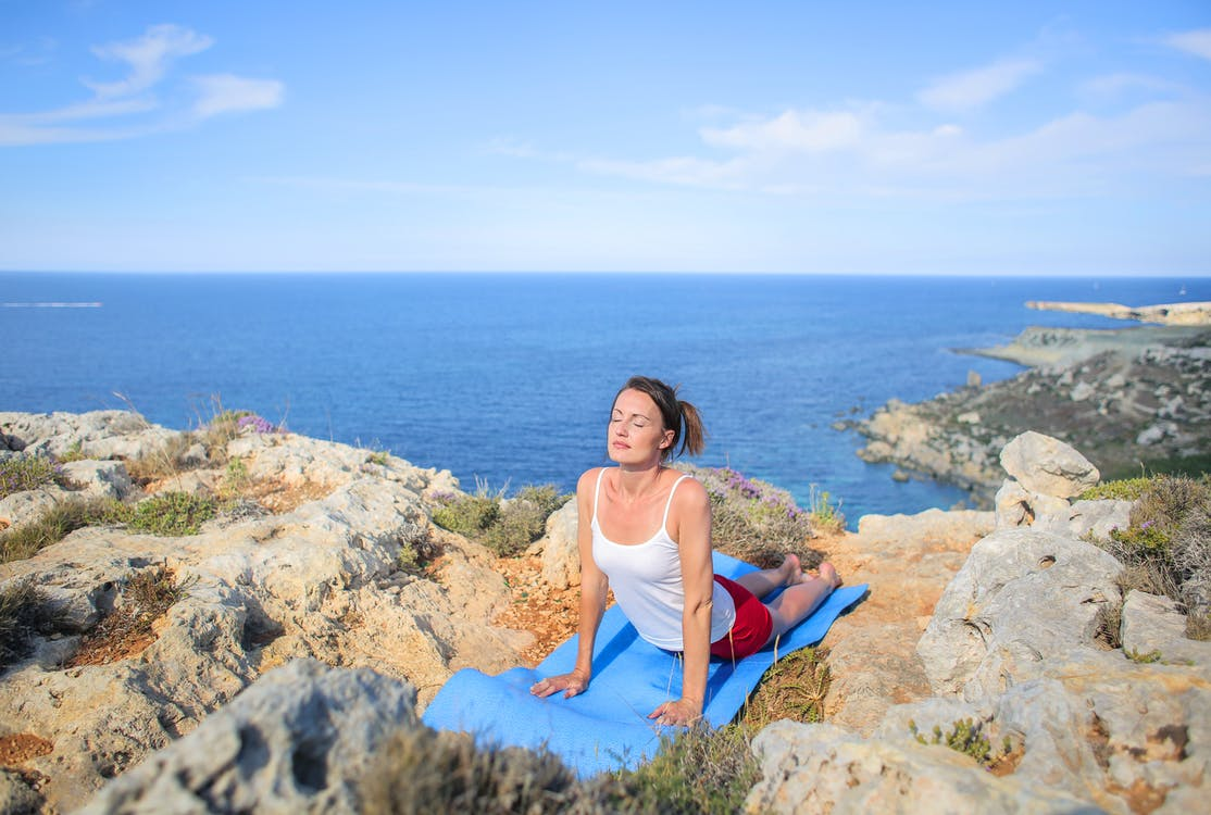 Woman in White Tank Top Doing Yoga Exercise On Rocky Shore