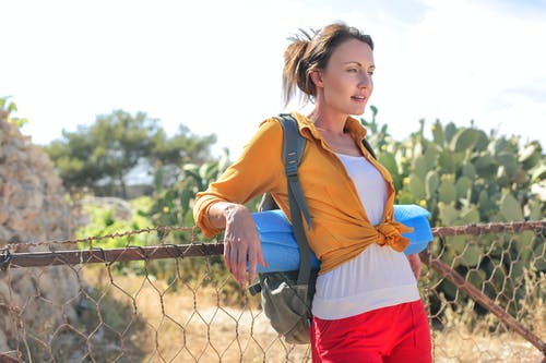 Woman Leaning on Cyclone Fence