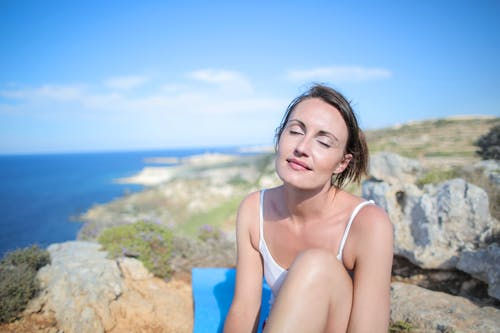 Woman in White Tank Top Sitting on Brown Rock Under the Blue Sky