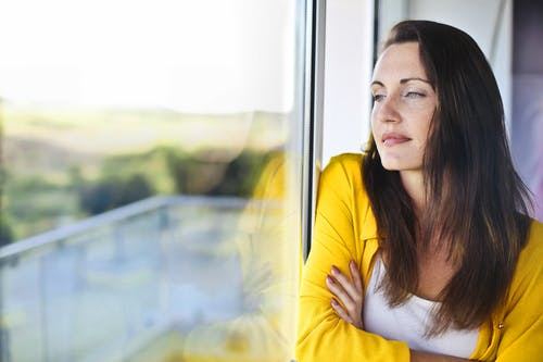 Woman in Yellow Long Sleeve Leaning on Glass Window