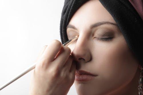 Woman Applying Cosmetics On Her  Eyelid