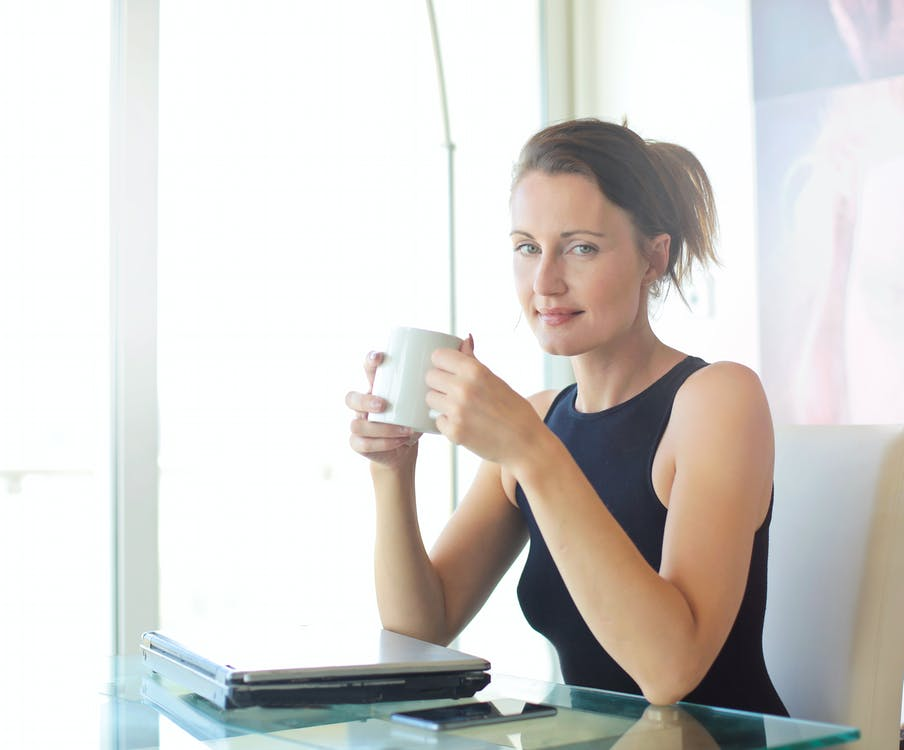 Woman in Black Tank Top Holding White Ceramic Cup