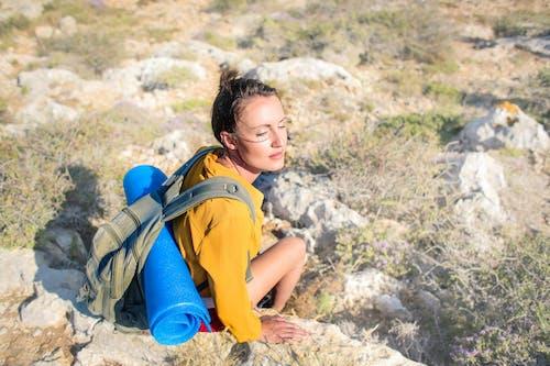 Girl in Yellow Long Sleeve Sitting On Brown Rock