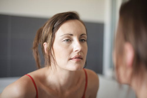 Woman in Red Tank Top Looking at The Mirror