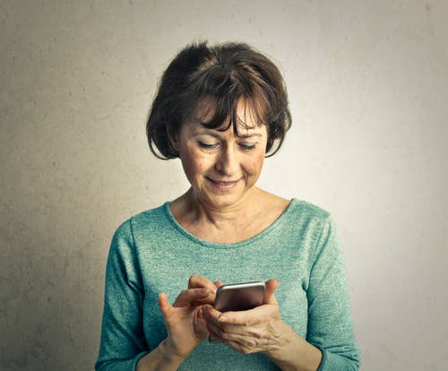 Elderly Woman in Green Long Sleeve Shirt is Having Fun Using Smartphone