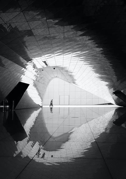 Grayscale Photo of Two Man Walking on Floor Tiles