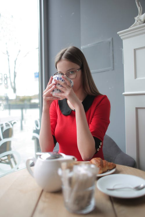 Woman in Red Long Sleeve Shirt Drinking Green Tea