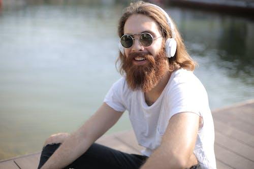 Man in White Crew Neck T-shirt Listening Music on White Headphones