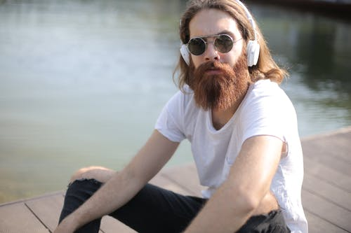 Man in White Crew Neck T-shirt Wearing Brown Sunglasses Sitting on Rock