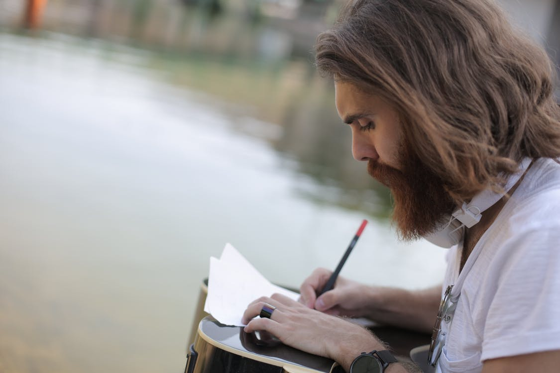 Man in White Shirt Writing on a Paper