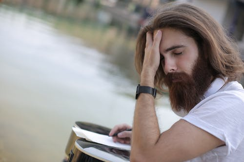 Young Man in White Shirt Having a Headache