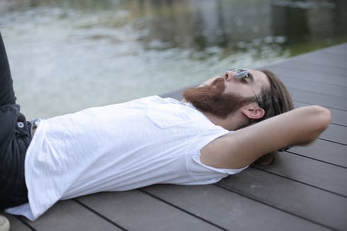 Man in White Shirt Lying Down on Wooden Aisle