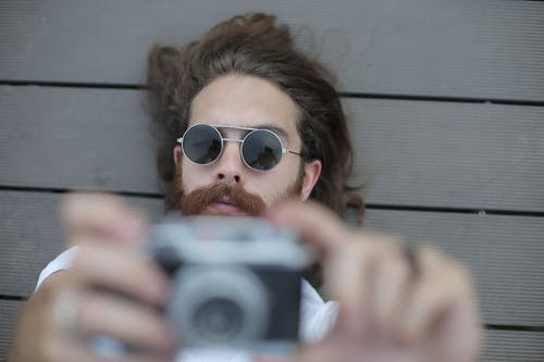Man in Silver Framed Sunglasses Holding Black and Gray Camera