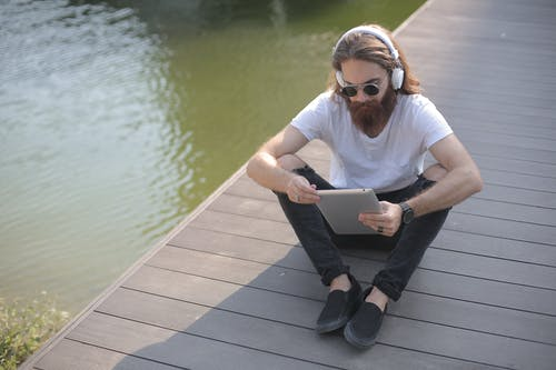 Man Wearing White Shirt and Black Jeans Listening to Music