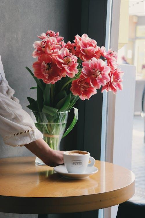 tay cô gái mặc váy trắng đặt lên ly cà phê trên bàn gỗ tròn bên cạnh lọ hoa màu hồng
