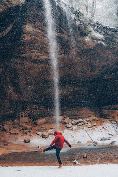 Man in Red Hoodie Standing Near Waterfalls