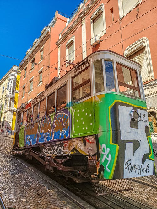 Green and Brown Tram Near Buildings