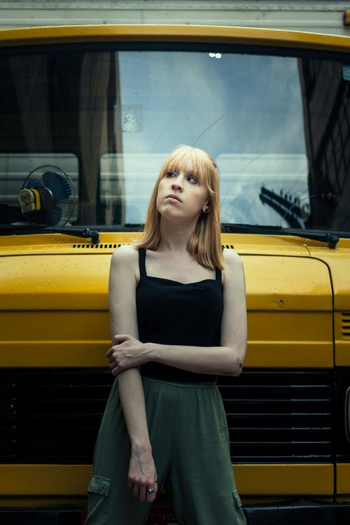 Woman In Black Tank Top Standing Beside The Yellow Vehicle