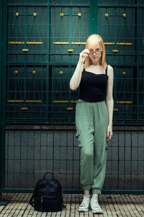 Woman in Black Tank Top and Green Pants Standing Beside Green Gate