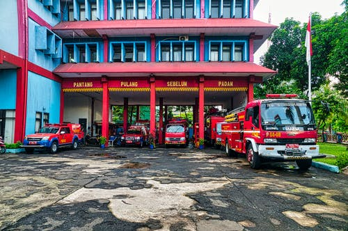 Fire Trucks Parked On Blue and Red Building