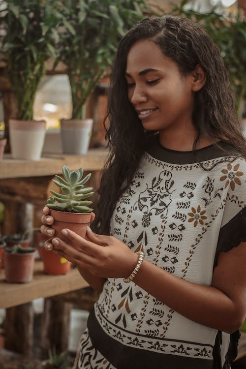Woman In White And Black Shirt Holding A Plant