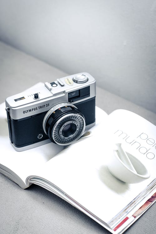 Silver and Black Camera on White Book