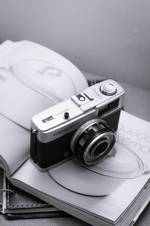 Black and Silver Camera on White Magazine