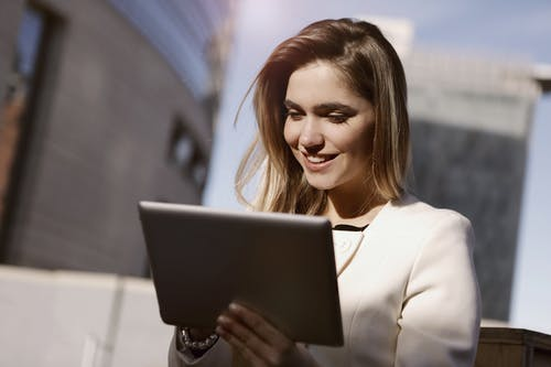 Woman in White Blazer Holding A Black Tablet
