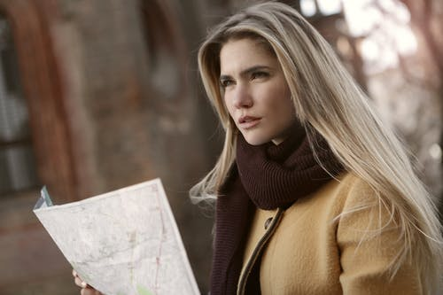 Woman In Brown Coat Holding A Map