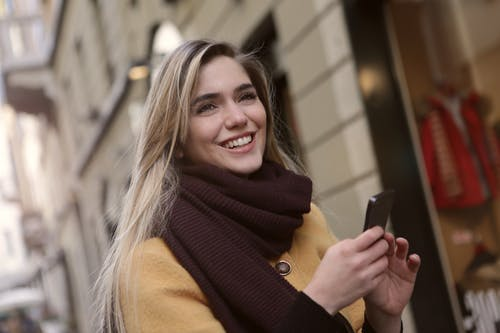 Woman In Brown Scarf Holding A Smartphone