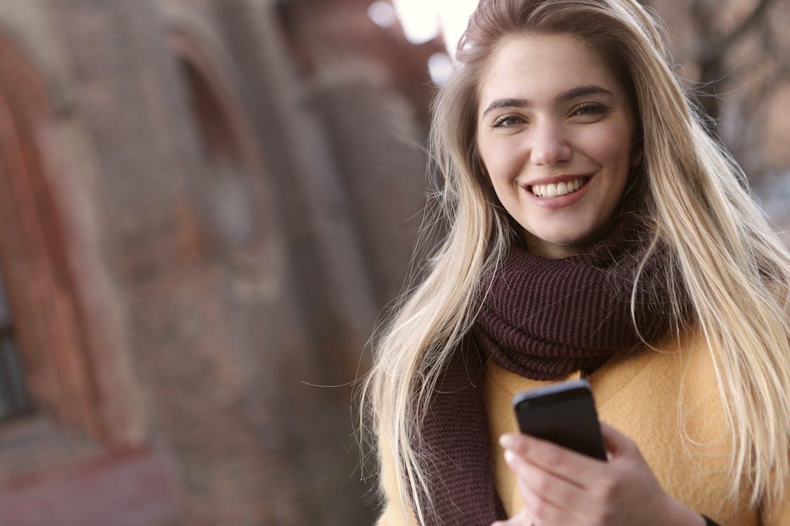 茶色のスカーフを身に着けている間微笑んでいる女性の浅い焦点写真