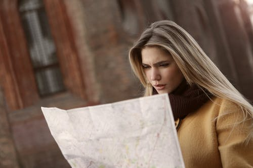 Woman in Brown Long Sleeve Shirt Holding Map