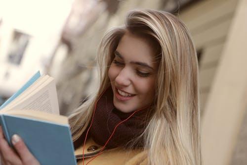 책을 읽는 동안 웃는 여자의 얕은 초점 사진