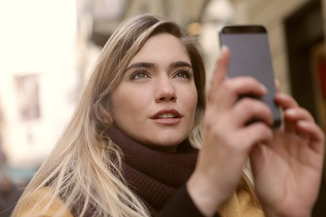 Selective Focus Photo of Woman Holding a Smartphone