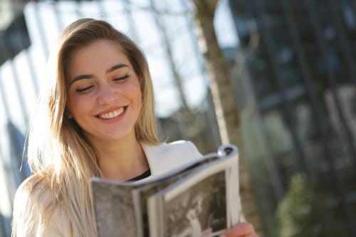 Woman in White Top While Holding Book