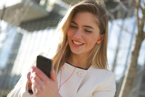 Smiling Woman In White Blazer Holding Black Smartphone