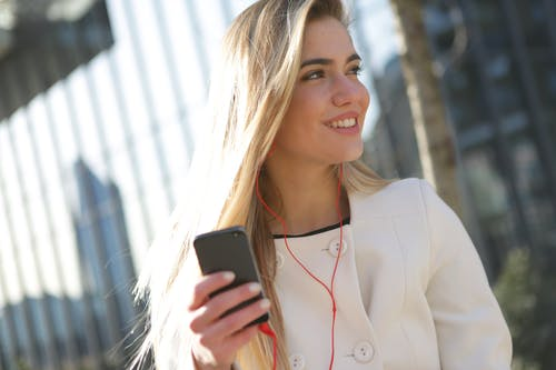 Smiling Woman In White Blazer Holding Black Smartphone