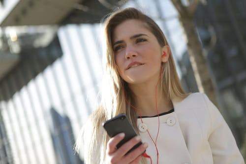 Woman In White Blazer Holding Black Smartphone