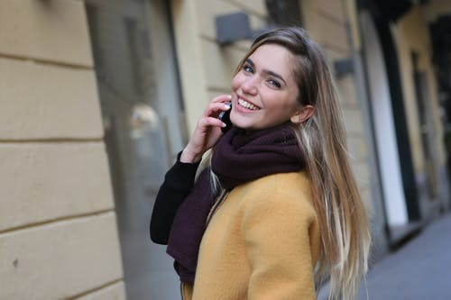 Woman in Brown Coat and Purple Scarf Holding Mobile Phone