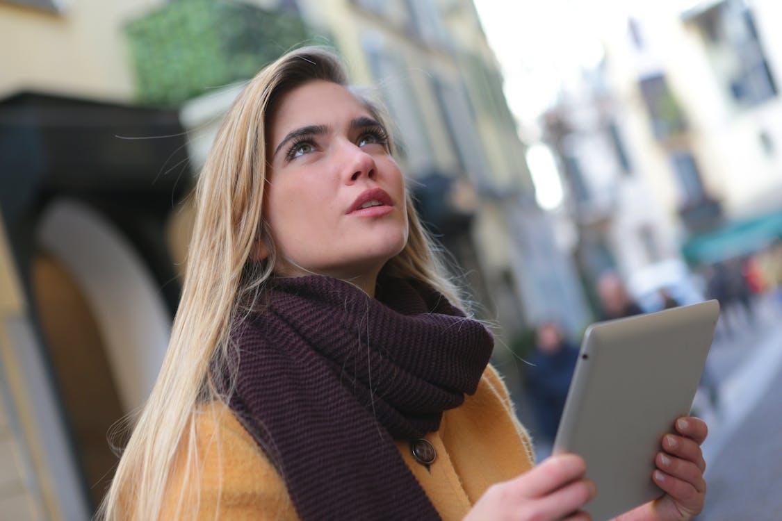 Wanita Dengan Mantel Coklat Dan Syal Ungu Memegang Tablet Perak
