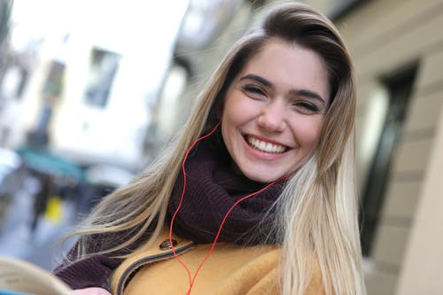 A Happy Woman in Purple Scarf Listening to Music