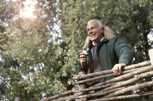 Man in Green Jacket Holding Brown Wooden Fence