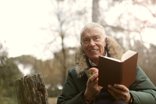 Man In Green Jacket Holding Brown Book